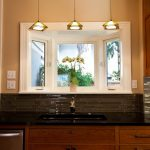 Three units of modern pendant light fixtures small window garden in the kitchen elegant black kitchen countertop black sink and gold tone faucet glass tiles kitchen backsplash
