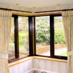 Tied corner window curtains glass windows with black trims metal rods and rod's rings
