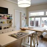 Transitional craft room idea with classic white painted storage system large and simple white crafting table cream surface work desk the cabinet system under windows hardwood floors a large pendant lamp