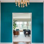 Turquoise color scheme for wall system modern pendant chandelier fixture fabulous entryway rug in blue and black colors darker stained wood floors a set of living room furniture a standing lamp