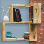 Unique corner book shelves made from non staining wood a pile of books an arrangement of books a small white porcelain vase and red brick wall system