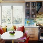 White round table with red plastic chairs and bench under windows plus its colorful pillows a kitchen set with colorful backsplash and white countertop a gas stove