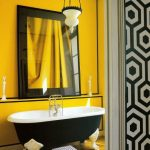 Yellow Painted Wall For Bathroom With Classic Monochromatic  Bathtub Classic Pendant Lamp Large Decorative Mirror With Black Frame Wood Planks Flooring Idea