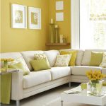 Yellow wall paint for living room with beautiful wall decorations small floating wood shelf for displaying free standing chandeliers L shape sofa in white plus white and yellow pillows white coffee table