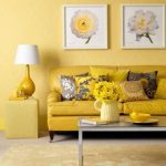 Yellow wall paint idea with diamond cut motif  beautiful yellow leather sofa plus floral patterned pillows a yellow Ottoman with table lamp glass top coffee table and two flower pictures framed in white