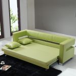 adorable soft green couch that turn into bed design with small pillows on black area rug aside tall glass window with stainless floor lamp