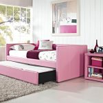 adorable sweet pink day bed with pop up trundle design with white floral patterned bolster and bar window and small armoire and fabric rug