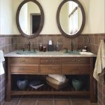 adorable vintage bathroom design with  rustic wooden vanity and twin woodne framed wall mirror on brown tile flooring