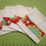 adorable white cloth napkin design with flashing red accent with floral pattern on green table cloth