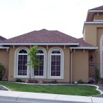 architectural house design with brown roof and arched white window with bar and green landscape and concrete patio with the most popular exterior house color of cream