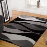 awesome black and gray area rugs decorated in living room with cozy gray armchair and office desk plus framed picture and hardwood floor and white brick wall