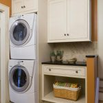 beautiful yellow accent in small laundry room with simple cabinet and storage with bin and smallest stackable washer dryer