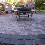brick paver calculator with stone in circle pattern with terrace chairs and round coffee table and pretty garden at backyard
