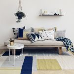 casual ferm living in usa with cream urban sofa design with geometrical skandinavian patterned cushions and round white coffee table on area rug with wall rack and hanging potted plant