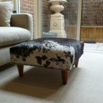 cow hide Ottoman with higher legs a comfortable sofa with pillows