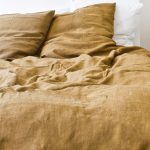 creamy golden linen sheet design to cover white bedding idea in white bedroom with golden pillows too
