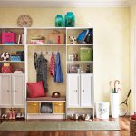 cute mudroom storage units decorated in entryway with wooden cabinets and entryway rug and hardwood flooring and umbrella storage plus vintage clock and loundry basket