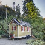 cute tiny mobile home that looks like house in yellow color with gray roof and small garden aside lush vegetation