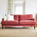 elegant red velvet pottery barn couch design in spacious room with corner table and white cushions on wooden floor with cream area rug