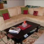 floral patterned rug on top of carpet for living room with cream sectional sofa and cushion plus wooden coffee table