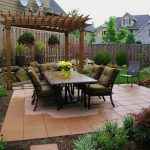 landscaping ideas for front of house and backyard with patio with tile flooring and seating plus table and wooden fence and stone plus green garden