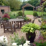 landscaping ideas for front of house with various plants and wooden seating and table