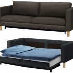 legendary black leather sofa that turn into bed design with white bolster and blue sheet and pillow with wooden legs