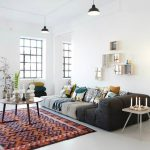 modern and minimalist ferm living usa with black velvet sofa design and tripod floor lamp and round coffee table on ethnic patterned area rug with bar glass windows