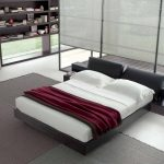 modern and spacious bedroom with gray tempurpedic sofa bed with white bolster and red sheet on gray area rug with open racks and floor lamp
