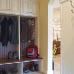 mudroom storage units in wooden with cabinets and cloth hooks and shoes storage and tile floor