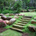natural landscaping ideas for front of house and with rock and metal fence plus garden light fixture
