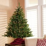 pre lit tabletop christmas trees with green tree combined with string light and red fabric on its roots and wooden table decoraded near the comfy sofa with cushions