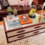 shabby chic kid friendly coffee table design with storage and glass top on patterned unique rug before brown leather sofa