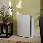 simple and small white air purifiers for smoker design on table aside black geometric vas with orchid flower