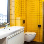 simple apartment bathroom design with white wooden vanity on large tile floor design with white toilet and small yellow tiles wall