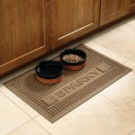 simple long lasting brown personalized dog mat for food and drink with two bowls on white tile flooring beneath wooden storage