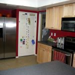 small kitchen with cute decorating idea such as red backsplash large electric stove black kitchen counter wood staining kitchen cabinets L shape kitchen island large metal covered refrigerator