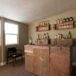 small wine bar design in rustic style a chair some wine bottles two floating shelves for displaying wine bottles