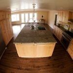 spaciouskitchen design with wooden cabinetry and double wide refrigerator idea on hardwood floor with modern lighting and big island