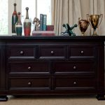 stunning and classic black dresser design with round botton beneath vintage metal decoration with ceramic beneath large glass window