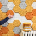 stylish modern soundproofing idea with honeycomb shape in light blue orange and white color on white wall of apartment