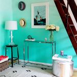 turquoise wall color in gradation style side table table lamp tiny legs table with glass surface small white rug with motifs wood floors staircase a painting hanging on the wall