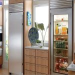 unique and small kitchen design with wooden cbainetry with tall and slim glass front refrigerator residential beneath the window