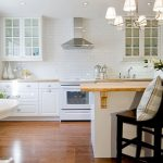 white ceramic tiles kitchen backsplash idea white kitchen cabinets glass door top cabinets with trims classic pendant chandelier fixture a kitchen island with wood top and black painted wood chairs
