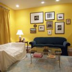 Yellow Paint Color Idea With Picture Frames  Dark Blue Sofa A Console Table Classic Table Lamp Transparent Glass Coffee Table Modern Light Blue Rug With Light Orange Motifs