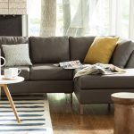 2 piece sectional sofa with chaise in grey with cushions and solid wood floor and round wooden coffee table and striped rug