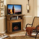 A corner TV stand with shelf and fireplace undermeath a single wall chandelier with glass wrap a rattan chair with brown knitted blanket a classic area rug with pattern