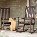 A pair of darker stained wood rocking chair design designed in mission style