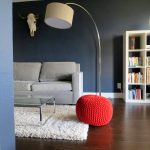 A white sofa with cushions white shag rug IKEA a red decortive chair a modern standing lamp glass and metal coffee table an open cabinet system for storing books collection