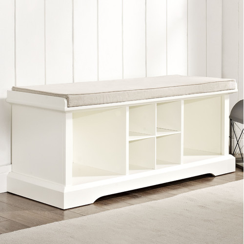 A White Wood Bench With Cushion And Shelves Underneath